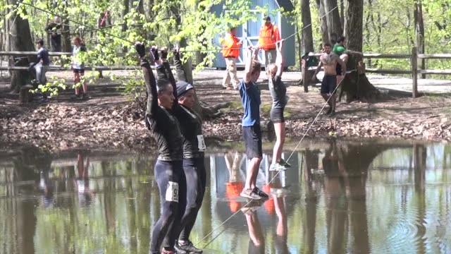 obstacle racers across pond on wires requiring strength and balance - tough mudder stock videos and b-roll footage