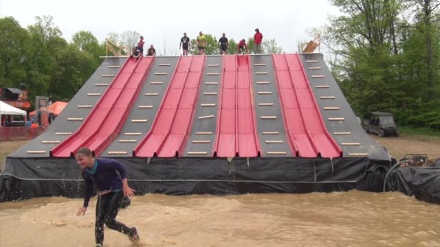 obstacle racers down slide into muddy water two shots good splashing - tough mudder stock videos and b-roll footage