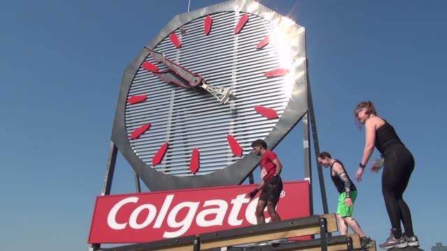 obstacle racers enjoy the challenge of the waterfront course in jersey city in front of colgate clock - salmini stock videos & royalty-free footage