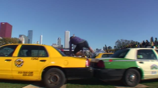obstacle racers in grant park in chicago climb over a wall jump over taxis and climb a net over a city bus urbanathlon - salmini stock videos and b-roll footage