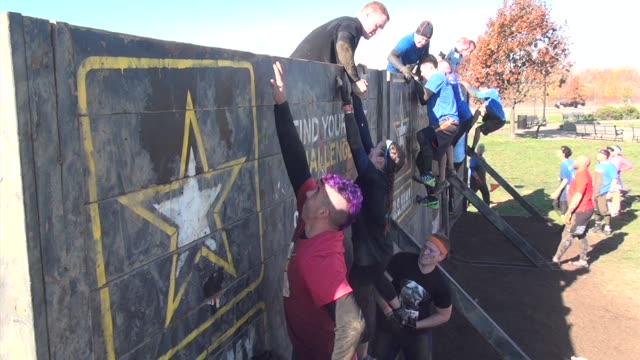 vídeos y material grabado en eventos de stock de obstacle racers take on a variety of challenges in liberty state park in new jersey across from one world trade center and lower manhattan - carrera de resistencia