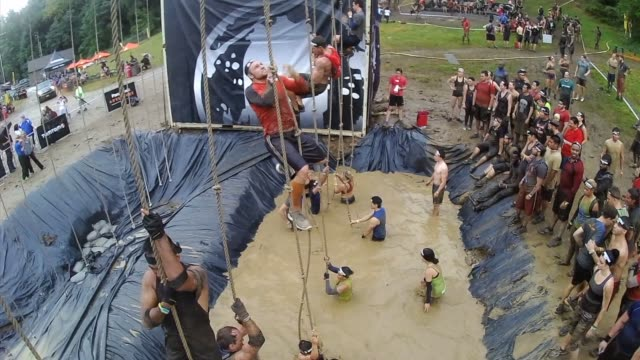 Obstacle racers take on fire pits barbed wire mud pits monkey bars rope climbs and extreme physical challenges