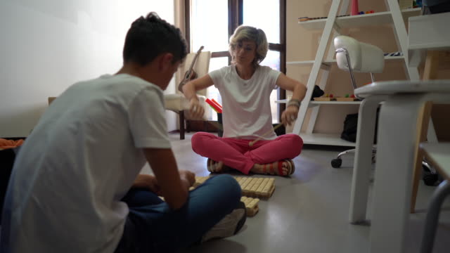 occupational therapist and boy playing wooden xylophone at rehabilitation center - invisible disability stock videos & royalty-free footage