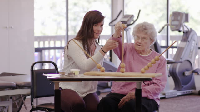 Occupational therapist working with a geriatric patient in a clinic