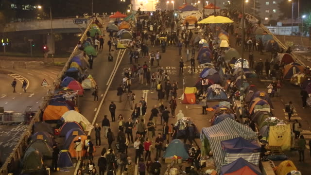 occupy hong kong protesters on a highway in hong kong china on december 10 wide shots and pans of pedestrians walking by occupy hong kong protesters... - occupy central stock videos & royalty-free footage