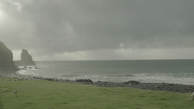 vidéos et rushes de ocean and rocky shoreline, grass in fg; isle of skye, scotland, uk - îles hébrides