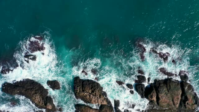 ocean blue waves break on high cliff of a rocky mountain. danger sea waves on a beach - 九份点の映像素材/bロール