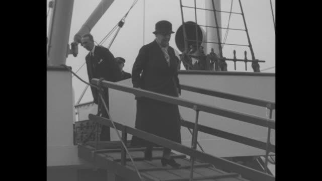 ocean liner approaches as it arrives in london harbor / queen wilhelmina of the netherlands walks down ship gangplank / princess juliana walks down... - 1935 stock-videos und b-roll-filmmaterial