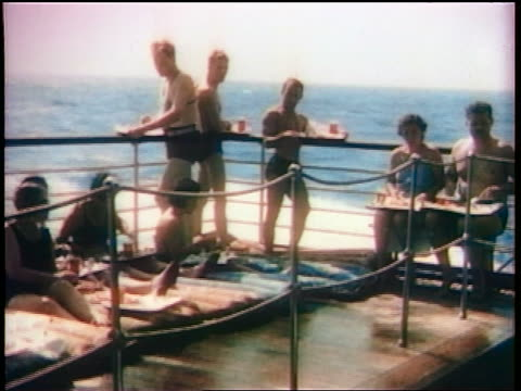 1936 ocean liner passengers in bathing suits lounging + eating on ship deck / ocean in background - passagier wasserfahrzeug stock-videos und b-roll-filmmaterial