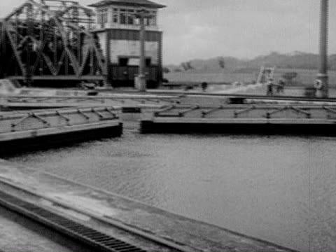 1934 b/w montage ms pan ha ws ocean liner passing through panama canal, people relaxing on deck, sluices opening, train engines on shore pulling liner through canal / panama canal, panama - panama canal stock videos & royalty-free footage