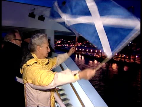 vidéos et rushes de ocean liner qe2 returns to clyde scotland greenock woman on qe2 deck waving two scottish flags qe2 pulled along river clyde by tugboat - remorqueur