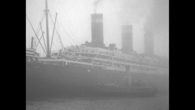 Ocean liner SS Leviathan arrives in fog in Southampton / Evangeline Booth in Salvation Army uniform walks down gangplank / CU General Higgins retired...