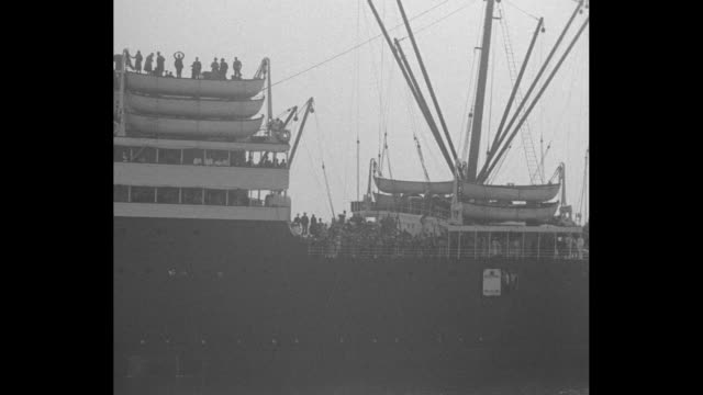 ocean liner ss republic seen beyond signal flags as it approaches shore steam whistle blares / roger williams and lewis yancey walk gangplank from... - コミッショナー点の映像素材/bロール