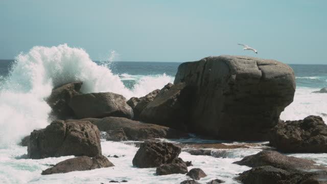 ocean water crashing against a rock - breaking wave stock videos & royalty-free footage