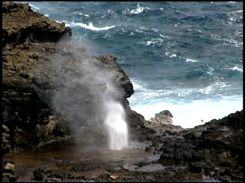 Ocean water spurts through a blowhole at a rocky coast in Hawaii.