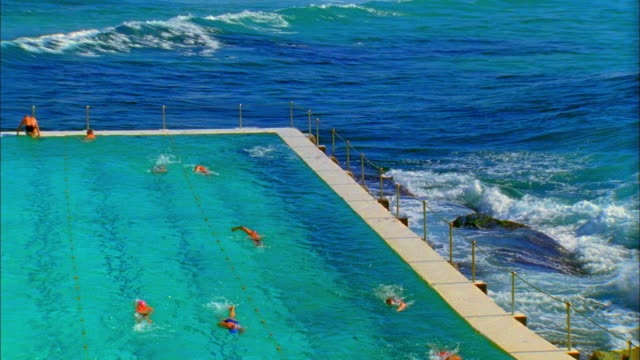 SLO MO WS HA Ocean wave splashing over edge of salt water pools with swimmers swimming at Bondi Icebergs pool, Sydney, Australia