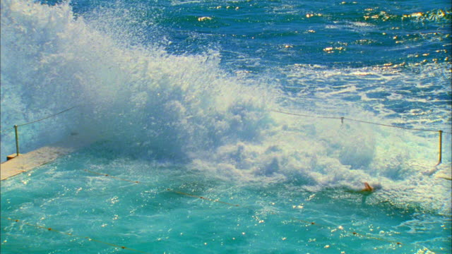 SLO MO MS HA Ocean wave splashing over edge of salt water pools with swimmers swimming at Bondi Icebergs pool, Sydney, Australia