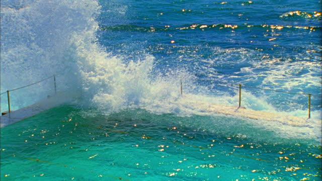 SLO MO MS HA Ocean wave splashing over edge of salt water pools with swimmers at Bondi Icebergs pool, Sydney, Australia