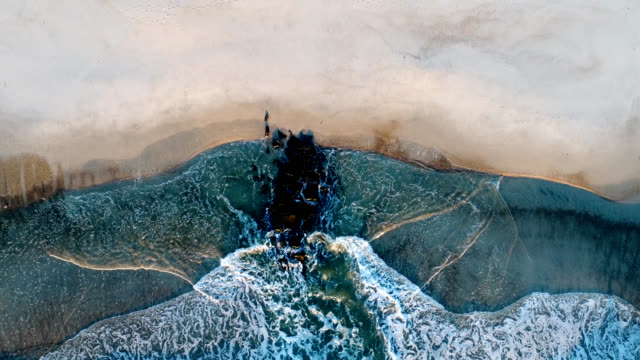 Ocean waves above rocks at water's edge. Aerial view