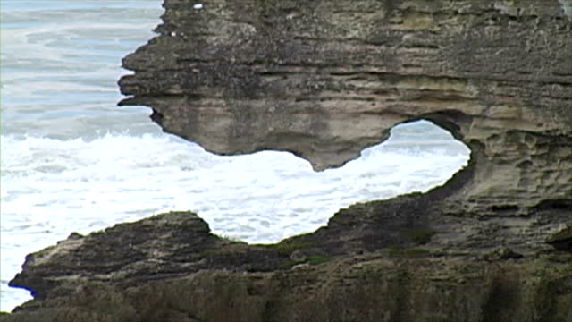 ocean waves are seen beyond a giant slate black rock. - slate rock stock videos and b-roll footage