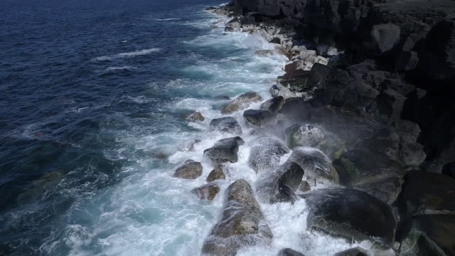 Ocean waves breaking on black lava coast, slow motion aerial