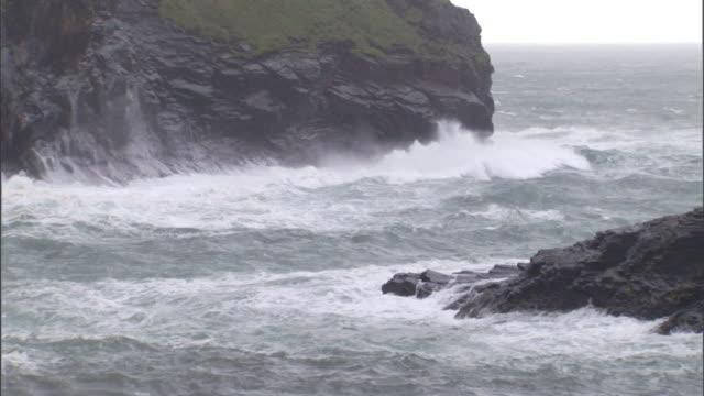 ocean waves crash against rugged cliffs. - cliff video stock e b–roll