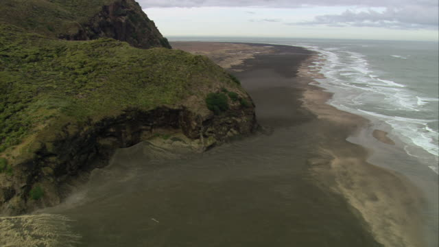 aerial ocean waves crashing against beach near green mountainous cliffs opening to expansive headland below / otago, new zealand - panning stock videos & royalty-free footage