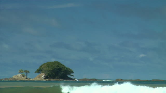 WS Ocean waves flowing past small island on Playa Uvita under blue sky / Puntarenas Province, Costa Rica