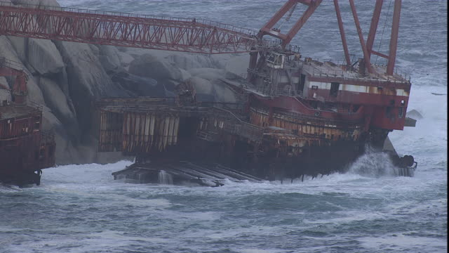vídeos y material grabado en eventos de stock de ocean waves hit an old rusty tanker ship crashed on rocks. - embarcación industrial