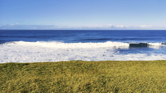 ocean waves in the background of a lawn field - french overseas territory stock videos & royalty-free footage