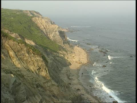 ocean waves lap against a beach at the bottom of a cliff. - ロードアイランド州点の映像素材/bロール