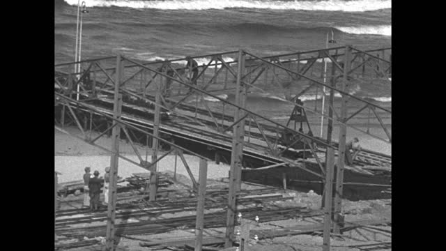 ocean waves roll in as construction workers work on a rail bridge at the shore line / note: exact month/date not known. documentation incomplete. - bridge built structure stock videos & royalty-free footage