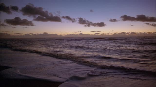 ocean waves roll onto a beach. - insel sylt stock-videos und b-roll-filmmaterial