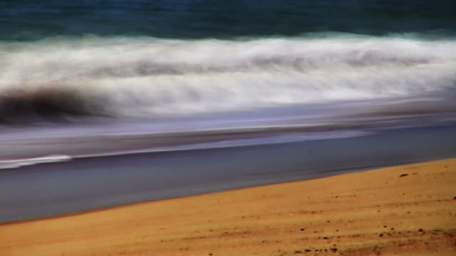 ocean waves roll onto a golden beach. - digital enhancement stock videos & royalty-free footage