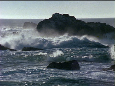 ocean waves roll up toward the shore and crash on the rocks. - televisione a ultra alta definizione video stock e b–roll