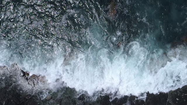 Ocean waves rolling on black lava coast, top down slow motion aerial