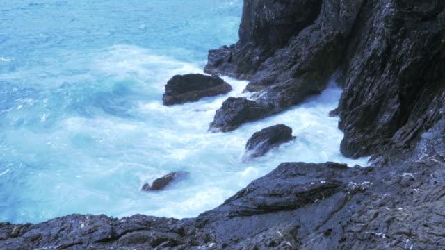 vídeos de stock e filmes b-roll de ocean waves splashing on rocky coast - alto contraste