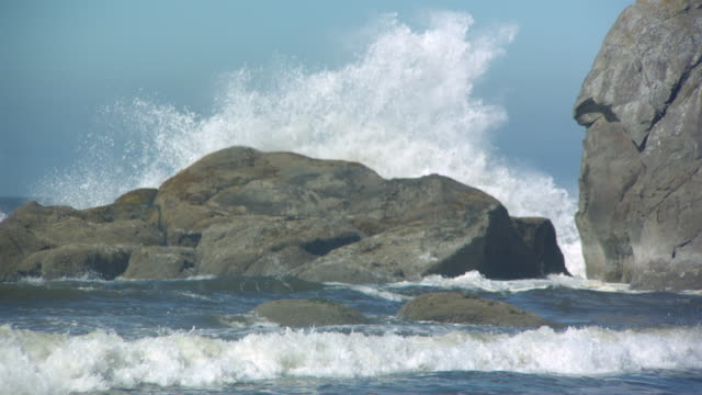 ws pan slo mo ocean waves spraying  on rocks in e sea /  washington, united states - 巨礫点の映像素材/bロール