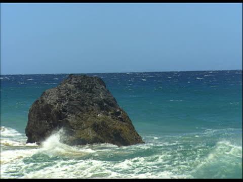 vídeos de stock, filmes e b-roll de ocean waves surrounding large boulder - boulder rock