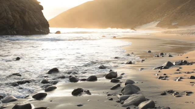 CU Ocean waves washing pebbles at Pfeiffer Beach at sunset, Big Sur, California, USA