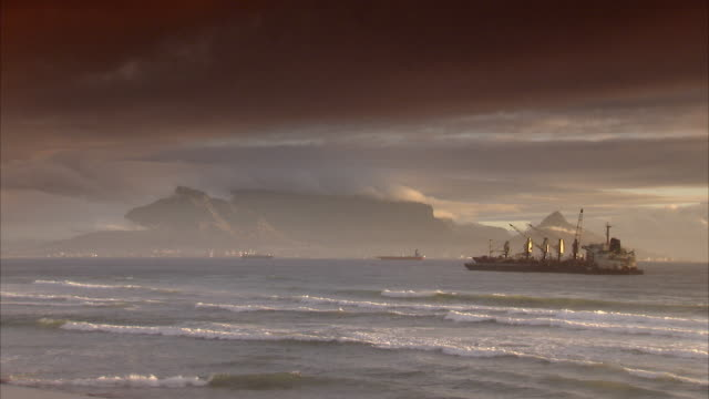 ws ocean waves with table mountain covered with clouds at sunset / cape town, south africa - ケープ半島点の映像素材/bロール
