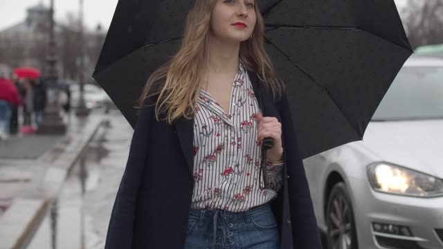 Oceane Grilhe wears a Stradivarius shirt Stradivarius jeans a Zara coat Mango shoes a Christian Laurier bag and a Kenzo umbrella outside the Elie...