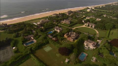 vidéos et rushes de low aerial, oceanfront mansions at  lily pond lane, east hampton, new york, usa - long island