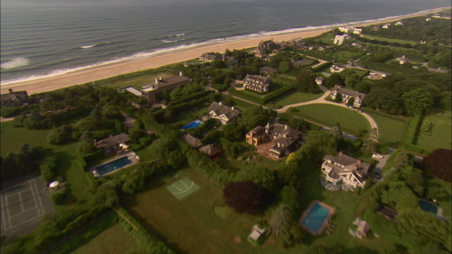 low aerial, oceanfront mansions at  lily pond lane, east hampton, new york, usa - long island video stock e b–roll