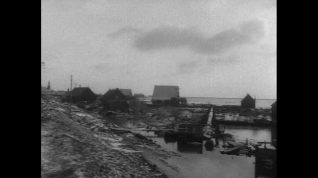 vs pan of ocean's shore to men working on seawall flooded farmland with windmill / heavily damaged building with snow on roof with water swirling on... - パイプオルガン点の映像素材/bロール