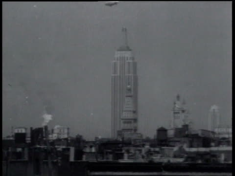 October 1, 1931 MONTAGE The Goodyear blimp Columbia delivering a package to the Empire State building / New York City, New York, United States