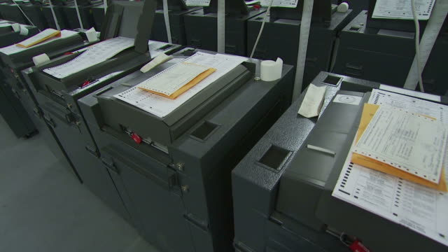 stockvideo's en b-roll-footage met october 13 2008 ds row of voting ballot counting machines as workers load other machines / new mexico united states - stembus