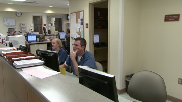 october 14 2009 pan hospital staff working behind the reception desk / memphis tennessee united states - ナースステーション点の映像素材/bロール