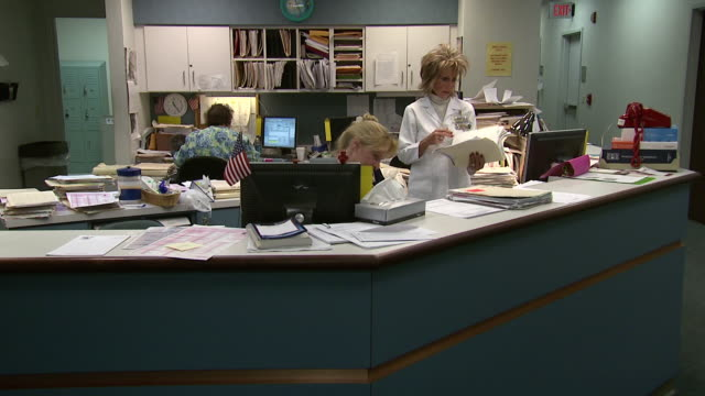 october 14 2009 zi staff members shuffling charts at nurses station at hospital / memphis tennessee united states - ナースステーション点の映像素材/bロール