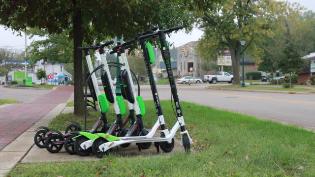 october 14, 2018; lime scooters are left parked on the sidewalk along kirkwood avenue after being juiced in bloomington, indiana. several weeks ago... - stationary stock videos & royalty-free footage